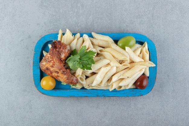 Aile de poulet avec pâtes penne sur plaque bleue.
