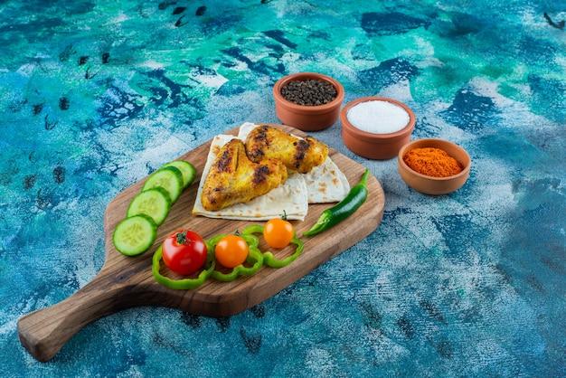 Ailes au four, lavash et légumes sur une planche à découper sur la surface bleue