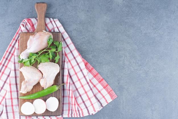 Ailes et cuisse de poulet cru sur planche de bois.