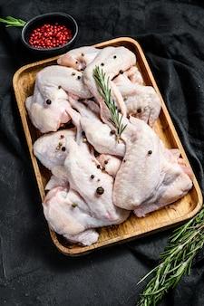Ailes de dinde crue dans un bol en bois, ingrédients de cuisine romarin et poivre rose, viande biologique de la ferme, vue de dessus.
