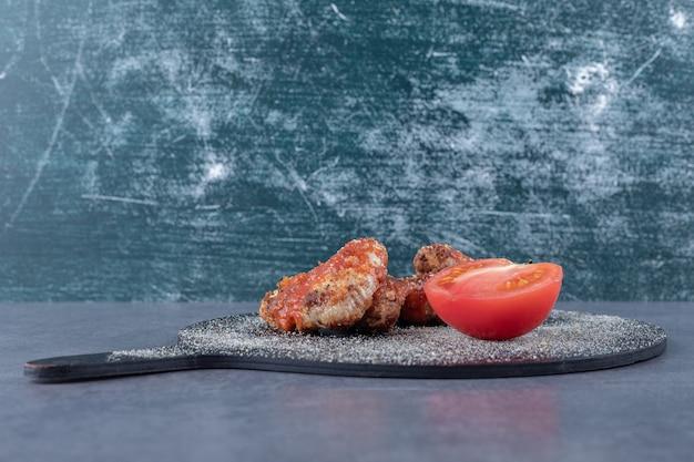 Ailes frites croustillantes et tomate sur tableau noir.