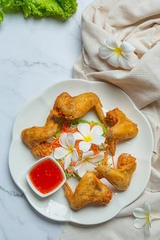 Ailes frites avec sauce au poisson, joliment décorées et servies.