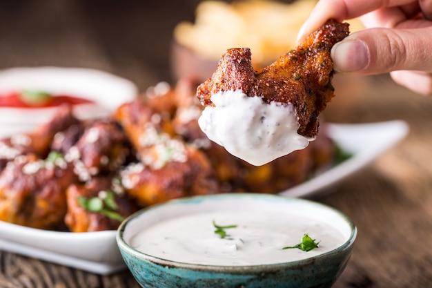 Ailes de poulet. ailes de poulet frites dans un bol blanc, vinaigrette à l'ail, ketchup et frites de pommes de terre.