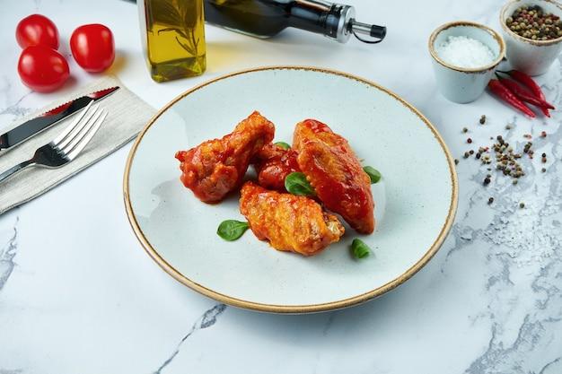 Ailes de poulet américain classique à la sauce buffle dans une assiette blanche sur une surface en marbre