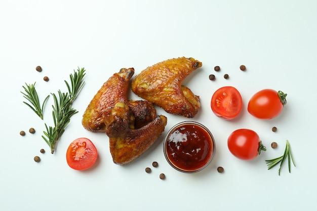 Ailes de poulet au four, épices et sauce sur fond blanc