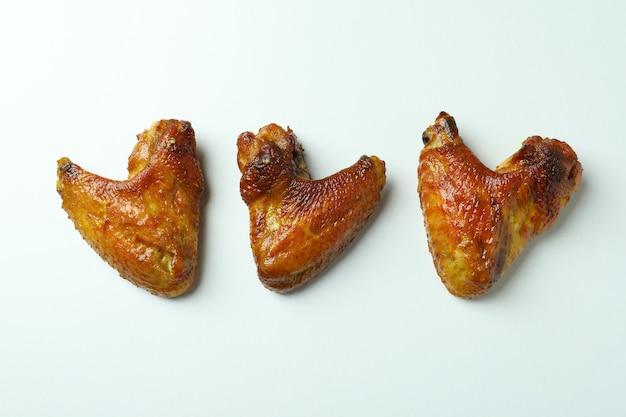 Ailes de poulet au four sur fond blanc, espace pour le texte