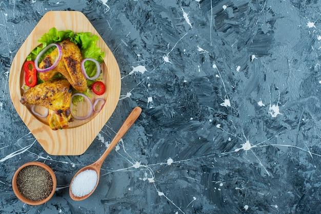 Ailes de poulet au four et légumes sur une assiette en bois, sur le fond bleu.