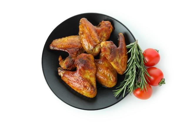 Ailes de poulet au four, tomates et romarin isolé sur fond blanc