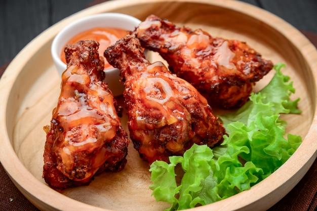Ailes de poulet bbq avec sauce chili épicée sur une plaque en bois