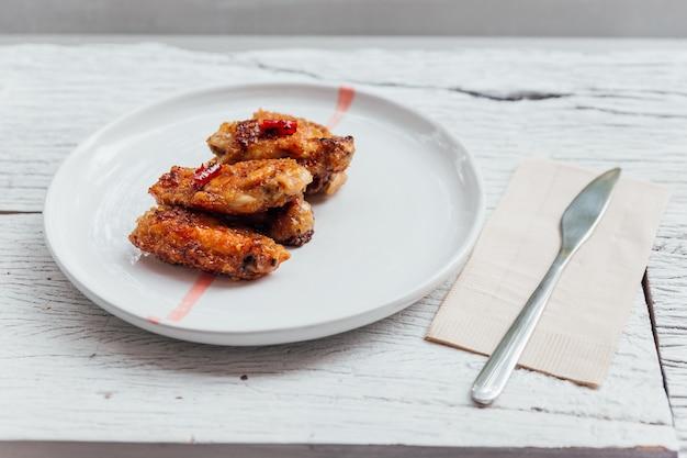 Les ailes de poulet coréennes sont remuées avec une sauce coréenne servie dans une assiette blanche.