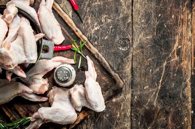 Ailes de poulet cru avec de l'ail et des herbes dans un bol. sur fond de bois.