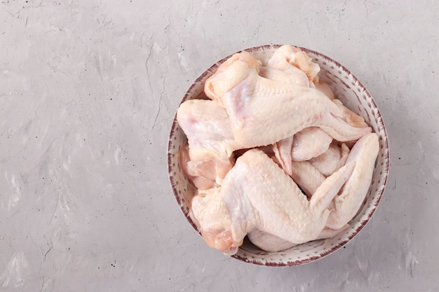 Ailes de poulet cru dans une assiette sur fond gris clair, vue de dessus, format horizontal, espace pour le texte