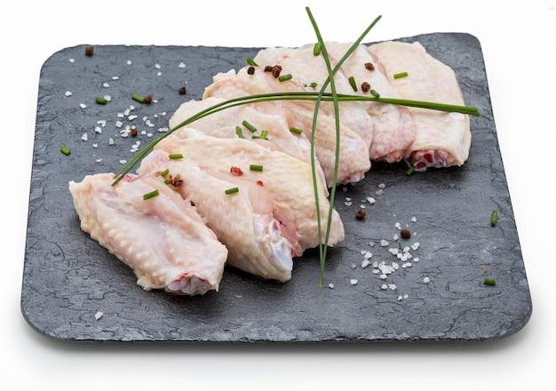 Ailes de poulet cru marinées avec du sel, du poivre et de la ciboulette sur ardoise isolé sur fond blanc.