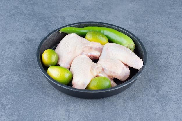 Ailes de poulet cru et piment sur plaque noire.
