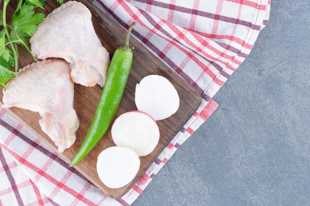 Ailes de poulet cru sur planche de bois.