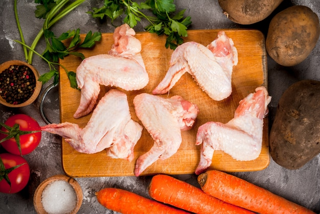 Ailes de poulet cru sur une planche à découper