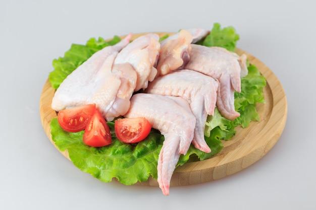 Ailes de poulet crues sur blanc