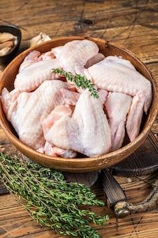 Ailes de poulet crues dans une assiette en bois avec du thym et de l'ail. fond en bois. vue de dessus.