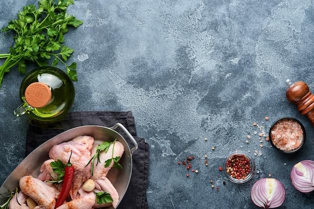 Ailes de poulet crues dans une casserole ou un bol en métal avec des épices et des ingrédients pour la cuisson sur fond d'ardoise gris foncé, de pierre ou de béton. viande crue aux épices au tableau noir. vue de dessus. maquette.