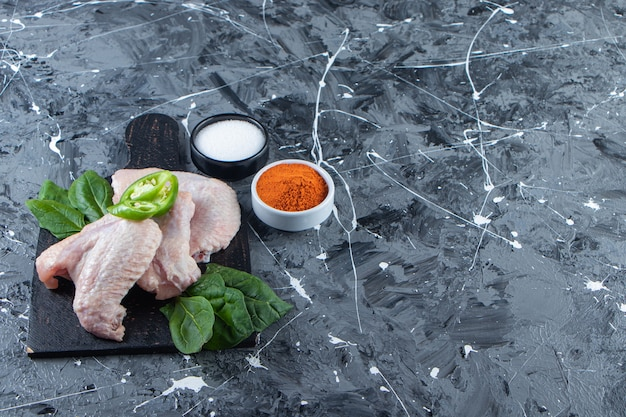 Ailes de poulet crues et épinards sur une planche à découper à côté d'un bol d'épices et de sel, sur fond de marbre.