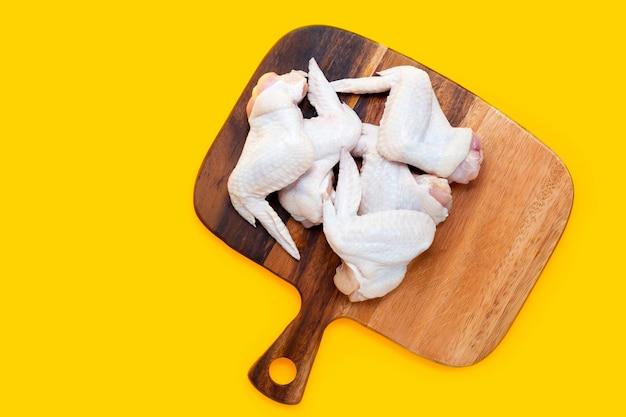 Ailes de poulet crues fraîches sur une planche à découper sur fond jaune.