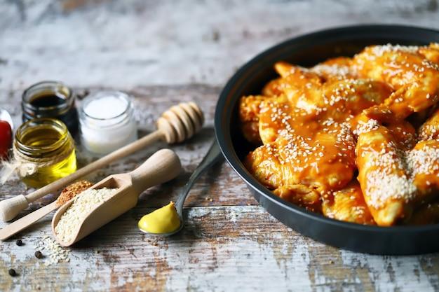 Ailes de poulet crues marinées dans une poêle avant la cuisson. cuisson des ailes de poulet. recette d'ailes de buffle. keto paleo. pegan.