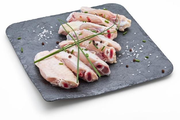 Ailes de poulet crues marinées avec du sel, du poivre et de la ciboulette sur une ardoise isolée sur une surface blanche