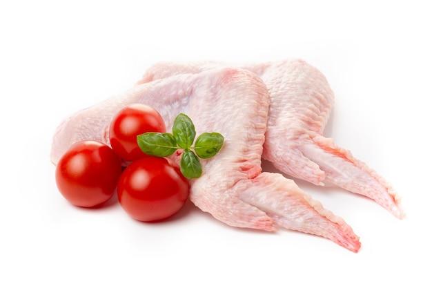 Ailes de poulet crues avec peau décorée de tomates et basilic sur fond blanc.