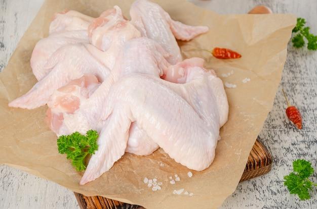 Ailes de poulet crues sur planche à découper avec piment à l'ail sel et persil sur fond de bois