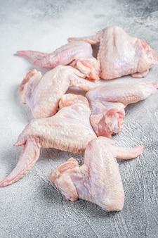 Ailes de poulet crues sur une table de cuisine. fond blanc. vue de dessus.