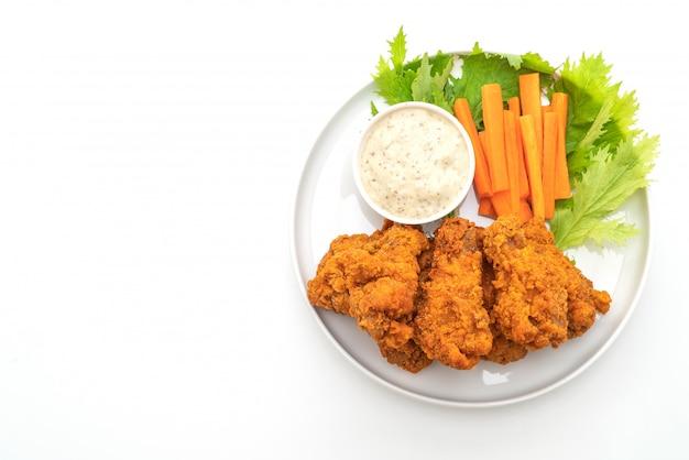Ailes de poulet épicées frites avec des légumes
