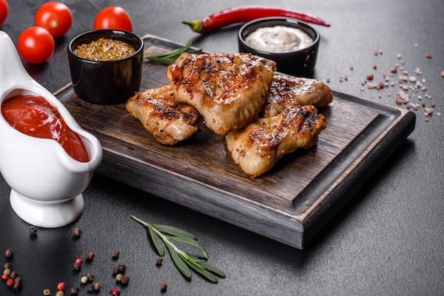 Ailes de poulet épicées grillées sur fond sombre avec épices et herbes