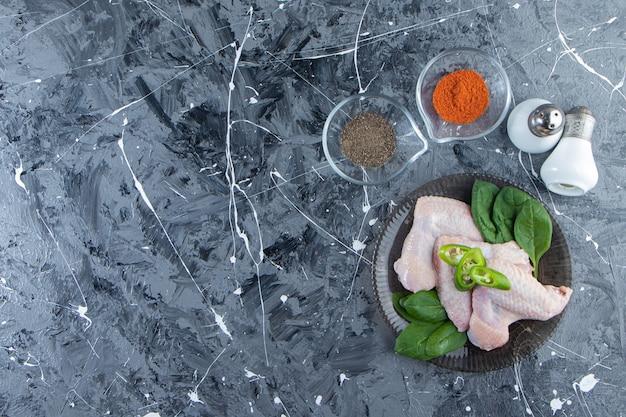 Ailes de poulet et épinards sur une assiette à côté de bols d'épices et de sel, sur fond de marbre.