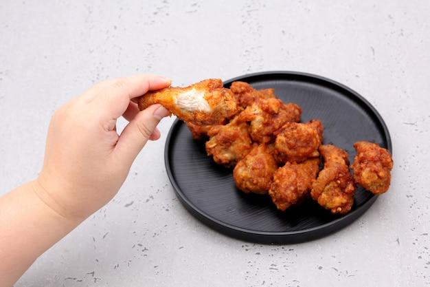 Ailes de poulet frit coréen isolé sur fond gris en studio.