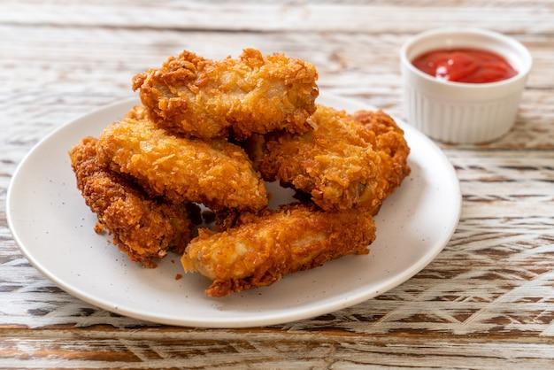 Ailes de poulet frit avec du ketchup - nourriture malsaine