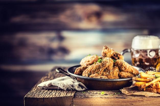 Ailes de poulet frit frites et bière pression sur table dans un pub ou un restaurant.