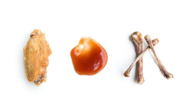 Ailes de poulet frit et os de poulet isolé sur fond blanc