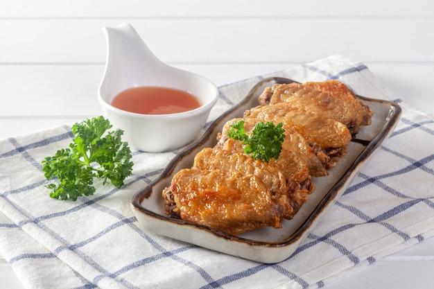 Ailes de poulet frit sur une table en bois blanche