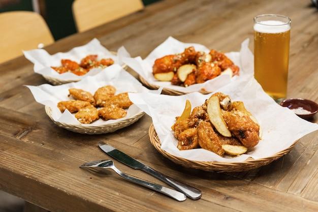 Ailes de poulet frites à l'ail coréen croustillant doré (huraideu-chikin de base) servies avec pommes de terre frites avec pelure. en corée du sud, le poulet frit est consommé comme repas, un apéritif avec de la bière froide.