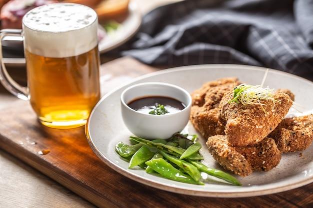 Ailes de poulet frites aux herbes de pois mange-tout et bière pression.
