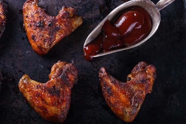Ailes de poulet frites sur le grill avec sauce bbq