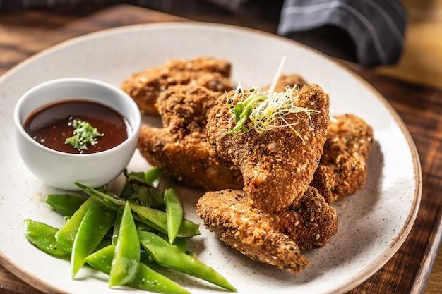 Ailes de poulet frites avec pois mange-tout et herbes.