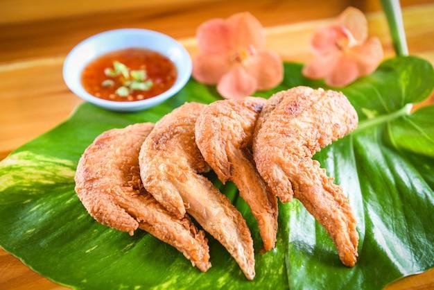 Ailes de poulet frites servies sur des feuilles avec sauce ailes de poulet croustillantes sur table