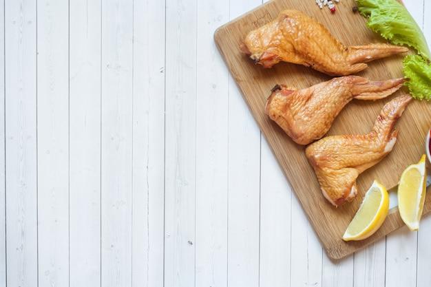 Ailes de poulet fumées avec laitue tomate fraîche et citron. espace de copie