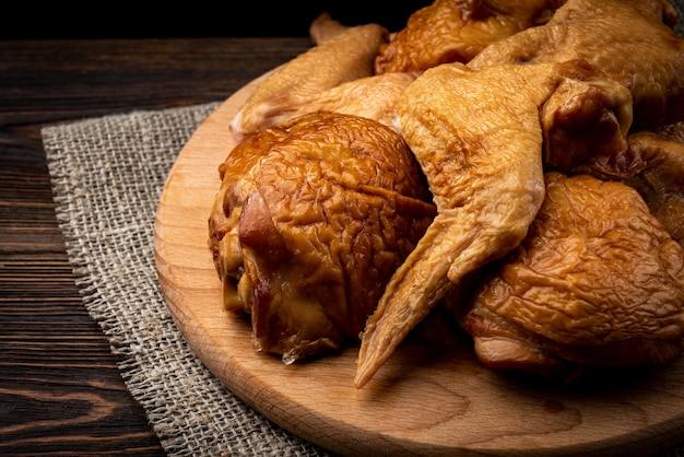 Ailes de poulet fumées sur planche de bois sur table en bois sombre.