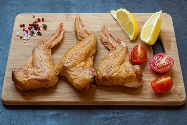 Ailes de poulet fumées sur une planche à découper en bois avec des légumes. fond sombre