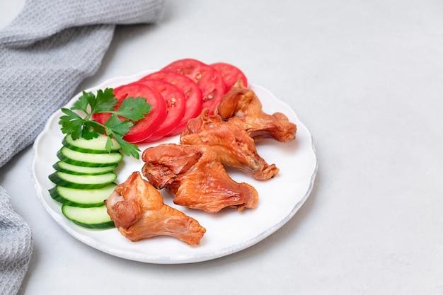 Ailes de poulet fumées sur plaque blanche avec salade d'accompagnement sur fond gris neutre copie espace