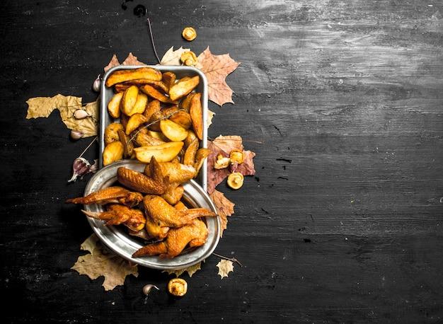 Ailes de poulet fumées avec pommes de terre frites.