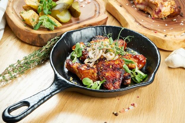 Ailes de poulet grillées au miel et à la bière servies dans une poêle décorative aux herbes. gros plan, mise au point sélective. mur en bois. photo culinaire
