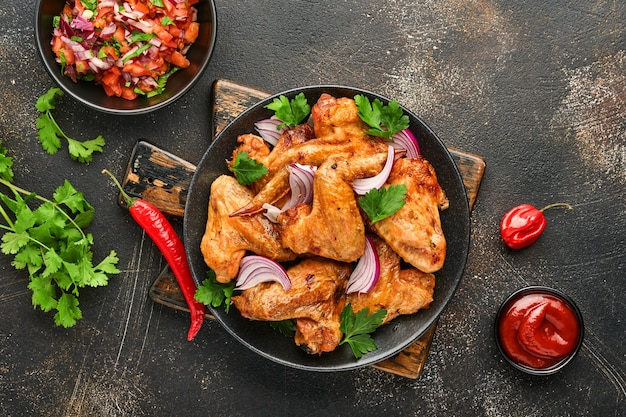 Ailes de poulet grillées ou barbecue rôti aux épices et sauce tomate salsa sur une plaque noire. vue de dessus avec espace de copie.